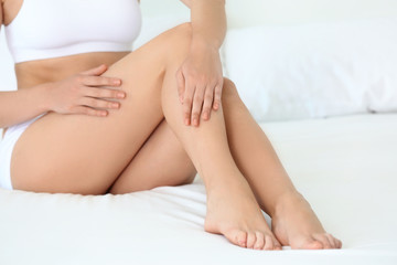 Young woman touching her leg on bed