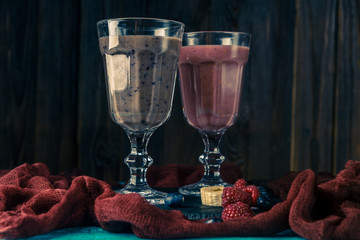 Image of two wine glasses with smoothies on table with cloth