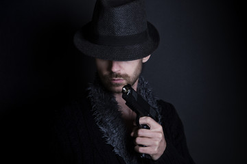 Mysterious man in the dark holding gun