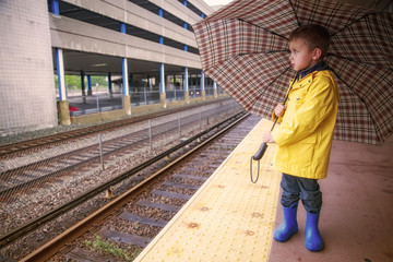 boy at the railway station in rain. cute kid in a yellow raincoat under an umbrella outside. The concept of commute. Copy space for your text