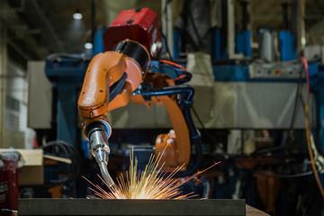 Orange industrial robot is welding assemblycar part in factory