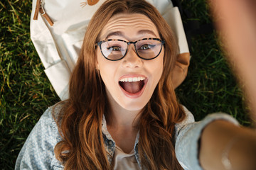 Close up top view of happy brunette woman in eyeglasses