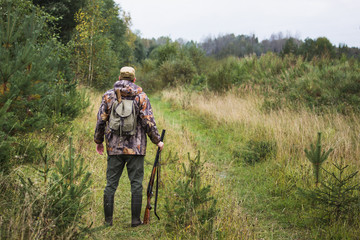 Hunter with a backpack and a hunting gun in the autumn forest. The man is on the hunt. Back view.