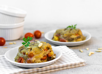 Homemade little cakes with aubergines, tomatoes, pine nuts and cheese. Mediterranean diet with summer vegetables. Italian healthy food.