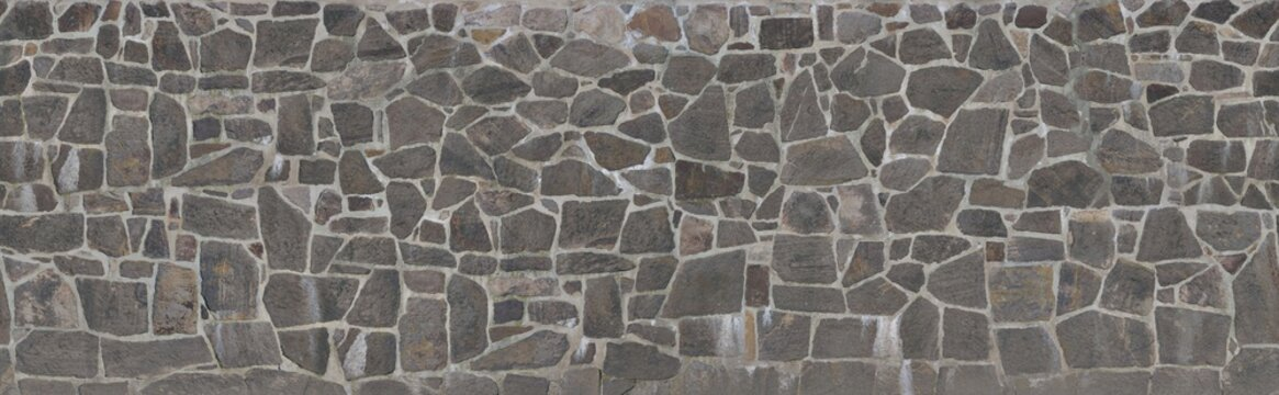 Texture of a stone wall. Old castle stone wall texture background. Stone wall as a background or texture. An example of masonry as a cladding of external walls.