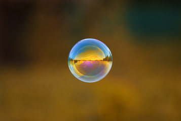 round iridescent soap bubble flying over the Sunny meadow with the mirrored landscape