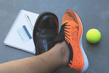 Life balance concept for work and exercise in top view half of business and sport shoes.