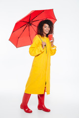Full length picture of happy african woman in raincoat