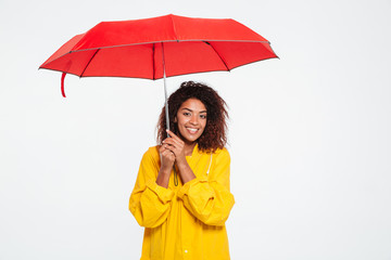 Picture of smiling african woman in raincoat hiding under umbrella
