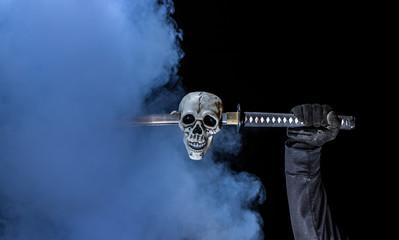 Gloved Hand Holding Sword Through Skeleton Skull
