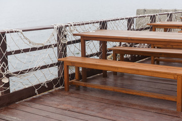 Image of tables in coastal cafe by sea