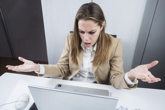 Manager vestita con giacca e camicia,seduta alla sua scrivania guarda il computer con stupore