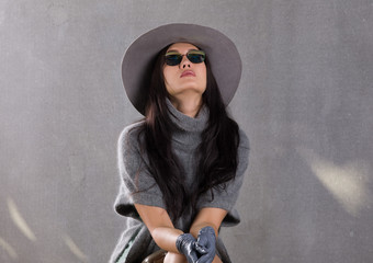 beautiful young woman in a gray sweater and gray hat on the background of a concrete wall