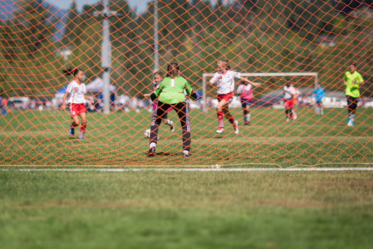 Young female soccer goalie in the net getting ready for a save during the attack