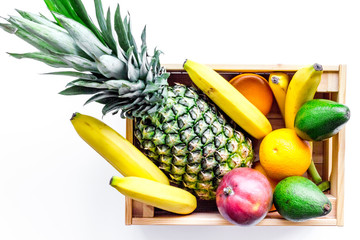 Sell friuts on the market. Bananas, oranges, mango in box and pineapple on white background top view