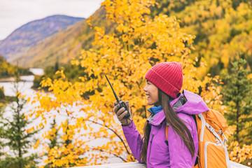 Woman talking on ham radio portable transceiver. Autumn hiker camping. Amateur radio operator woman speaking on handheld walkie-talking in mountains nature.