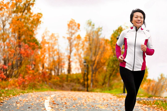 Mature happy middle age woman jogging outside in her 50s. Middle aged Asian chinese girl in her fifties jogging outdoor living healthy lifestyle in beautiful autumn city park in colorful fall foliage.
