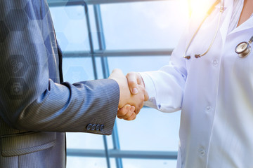Doctor shakes hands with patient .