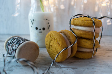 festive halloween pumpkin cookies with decorations and milk