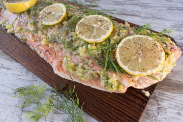 prepared salmon flank on board with dill and lemons