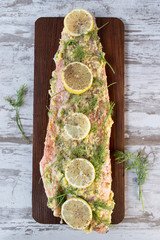 top view prepared salmon flank on board with dill and lemons