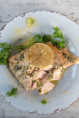 top view salmon with lemon and parsley on plate