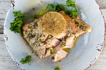 salmon with lemon and parsley on plate top view