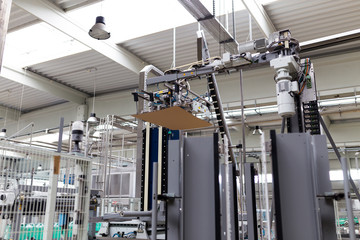 Industrial factory indoors and machinery. Automated robotic arm for packing.