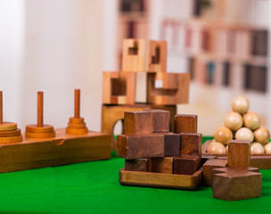 Wooden block brain teaser puzzle on green table in a blurred background