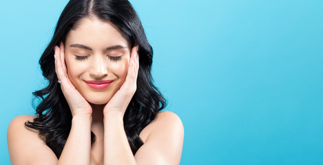 Beautiful young woman touching her face in skin care theme