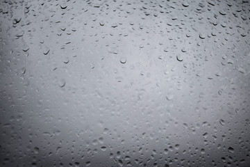 Drops of rain on a grey window glass. Close up   detail of a wet surface water with copy space