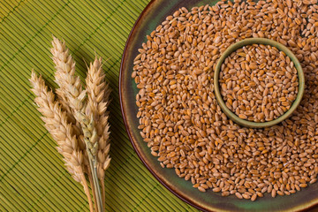 Grains and spikelets of wheat on a green background. Top view.