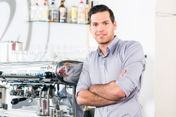 Portrait of confident young man posing near a modern automatic coffee machine