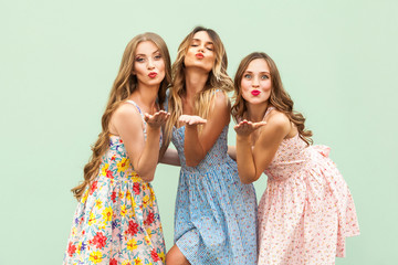 Sending air kiss. Three best friends posing in studio, wearing summer style dress against green background.