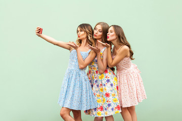 Happiness three young adult model, macking selfie and send air kiss in screen smart phone on green background.