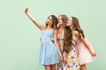 Beautiful three young adult fasion model, macking selfie, grimacing and tongue out. Green background.