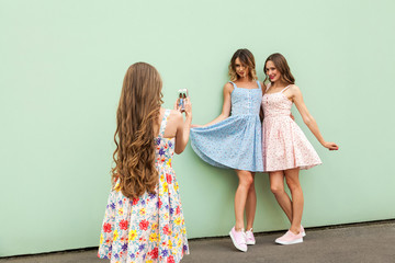 Young adult fashion model taking photo with a smart phone.