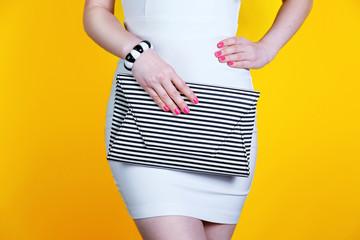 Wall Mural - Close up fashion girl with striped handbag near yellow wall