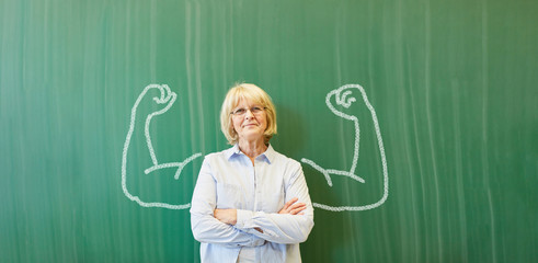 Starke Frau als Lehrer vor Tafel mit Muskeln Wall mural