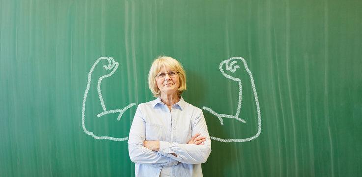 Starke Frau als Lehrer vor Tafel mit Muskeln