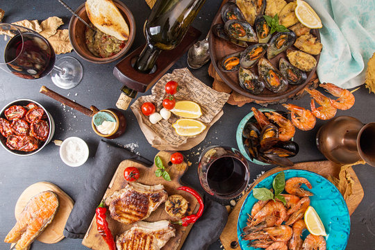 Overhead of dinner table. Assorted delicious grilled barbecue meat and seafood with vegetable. Pork grilled steaks, trout, mussels, shrimps, dried tomato, cherry tomato, glasses of red wine.