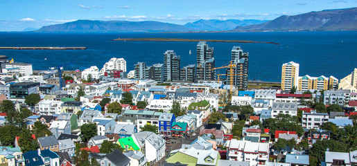 Fotomurales - Beautiful super wide-angle aerial view of Reykjavik, Iceland with harbor and skyline mountains and scenery beyond the city, seen from the observation tower of hallgrimskirja