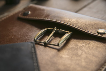 Close up of brown leather handmade handbag with bronze clasp on wooden table