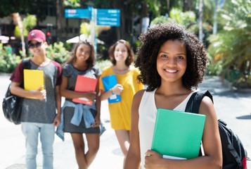 Schöne afrikanische Studentin mit anderen Stundenden in der Stadt