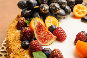 honey cake decorated with fruits and berries, decorate with gold kandurin, grapes, figs, kumquat, decorate with golden candurin, gold lace stand, menu idea