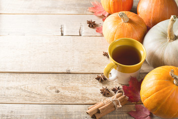 Cup of tea with pumpkins and cinnamon over wood texture