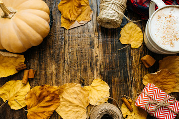 Pumpkin spiced latte or coffee in cup, dry leaves, gifts on a vintage table. Autumn background