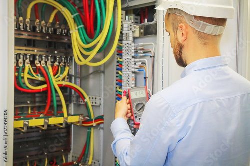 electrical engineer with multimeter on background of distribution