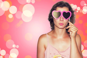 Beauty Young fashion model Girl with Valentine heart paper glasses on pink background. Love. Valentines Day gift.