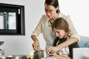 Woman Assisting Daughter In Preparing Cupcake